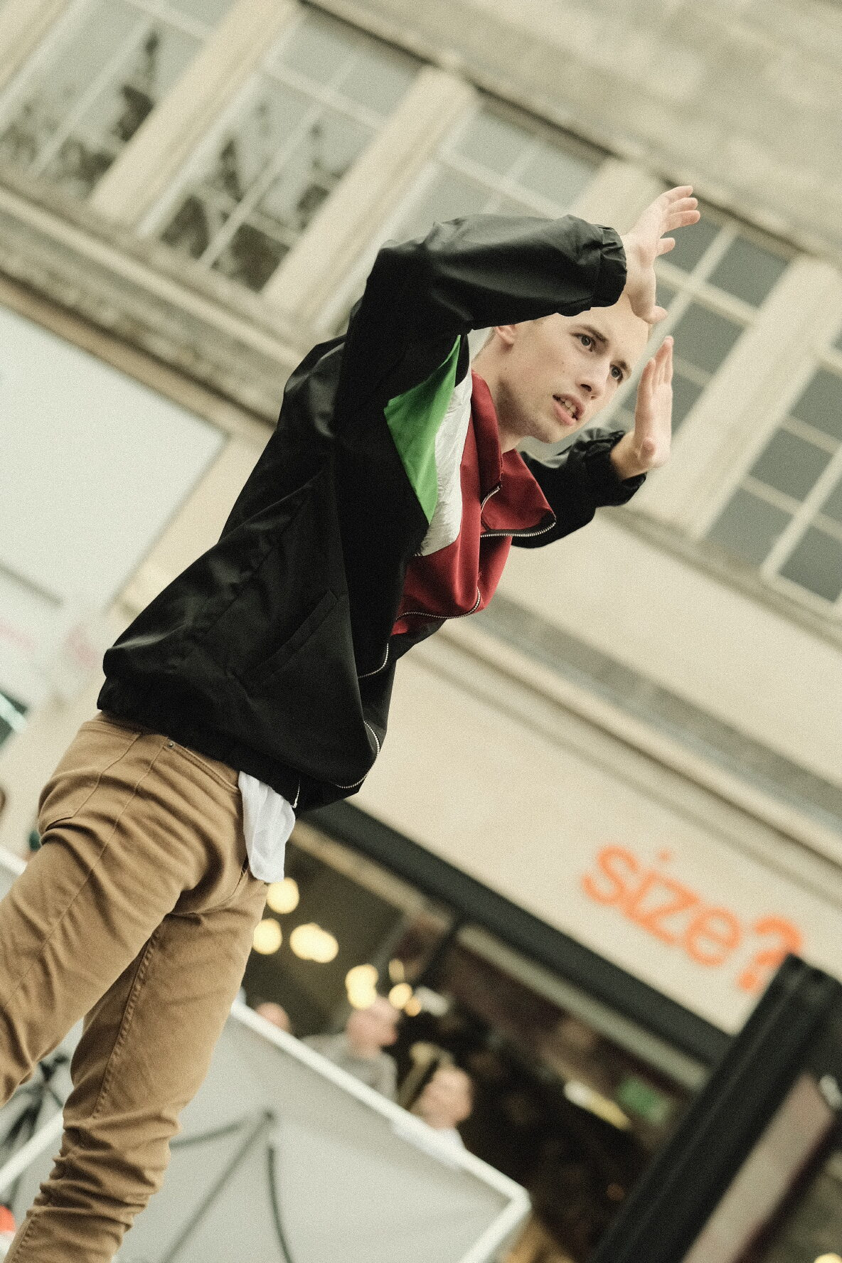 A portrait photo of a young male dancer with his hands in the air (like you would if you were getting arrested)