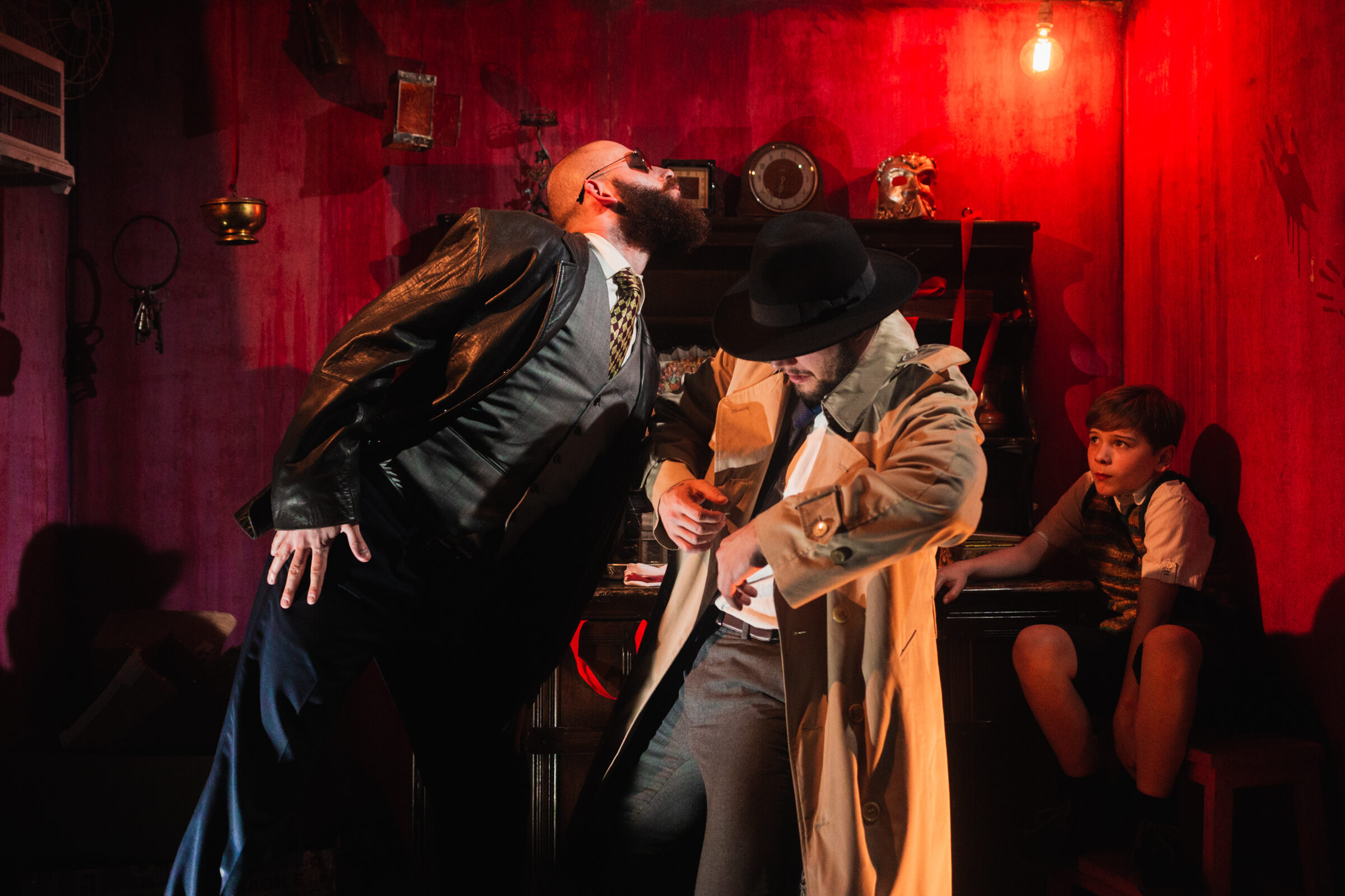 Bald white man with large beard leans as if to sniff the air. He is dressed in a shirt, trousers and waistcoat and is wearing a long black leather coat. Next to him is a white man wearing a black hat and long beige trench coat. They are in a theatre set with red walls, low lighting and a lightbulb. A boy sits in the corner of the room at the back.