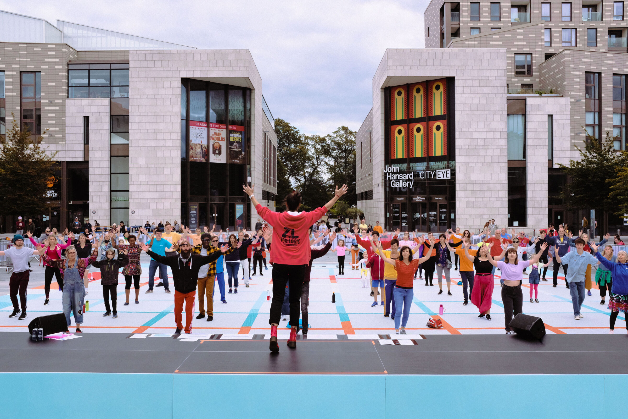 Participants performing in a socially distanced grid all hold their arms up in the air