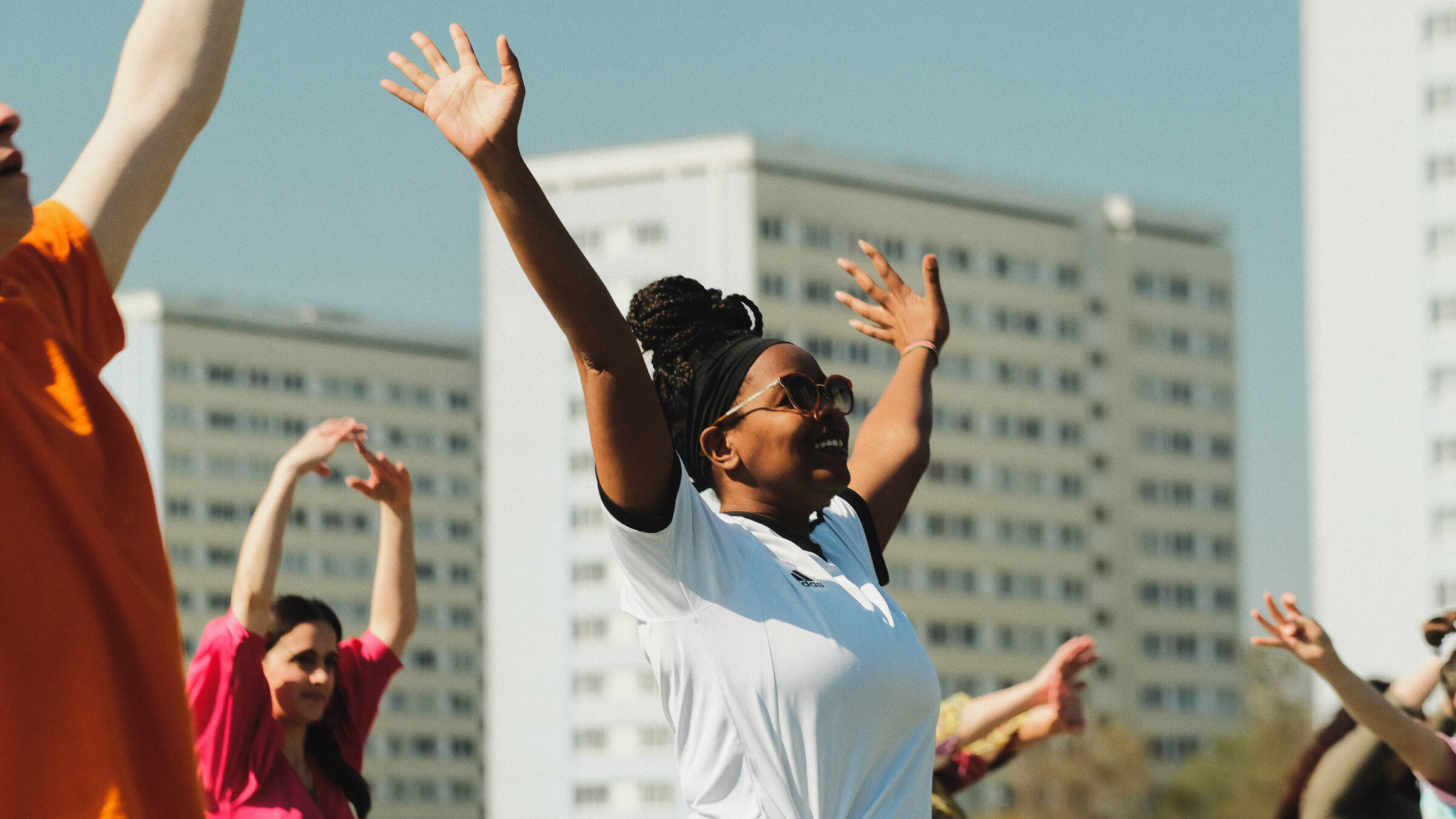 A woman stands with her arms raised as part of a dance event