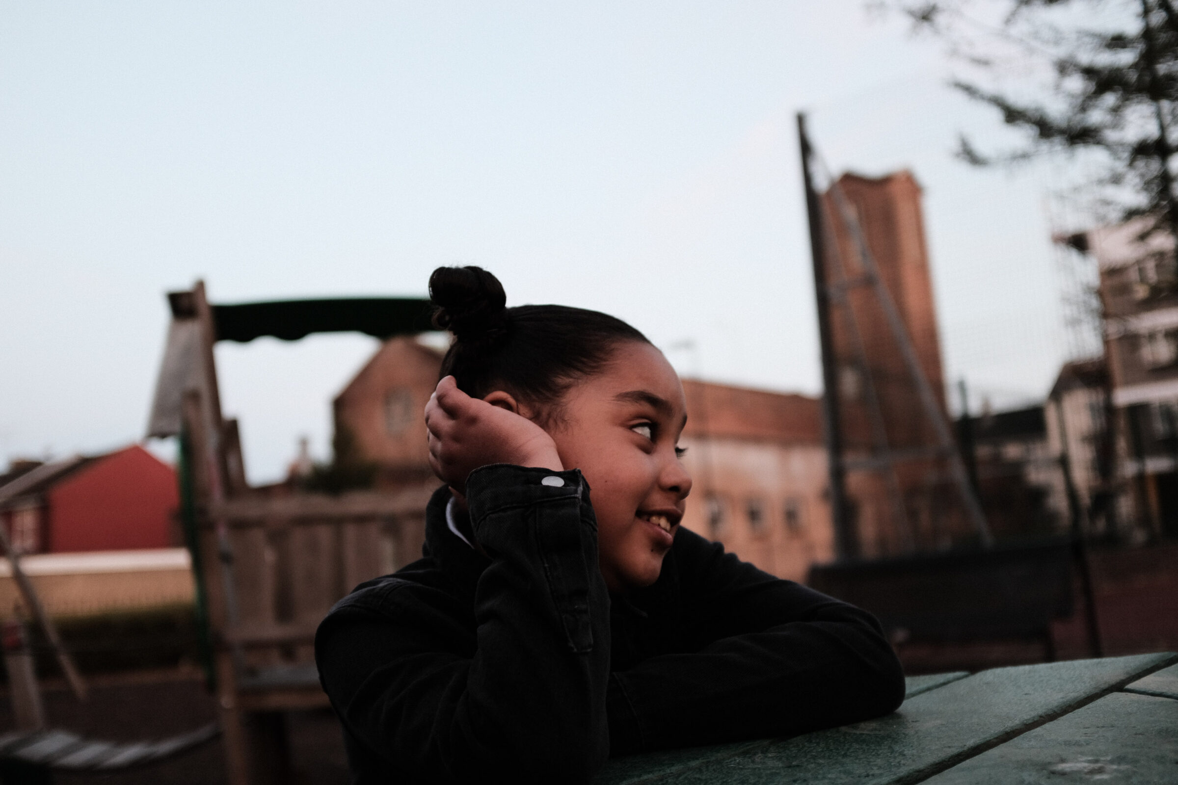 A girl poses for a picture while leaning on a picnic table and looking towards the right