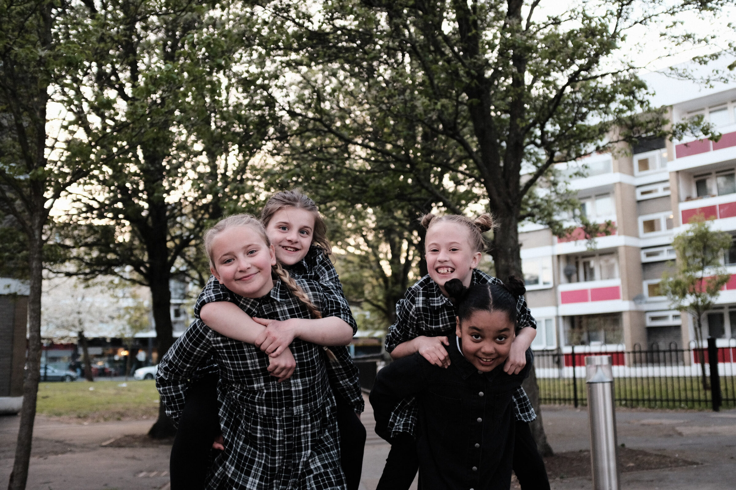 Four girls pose for a picture in a park area, with flats and trees in the background