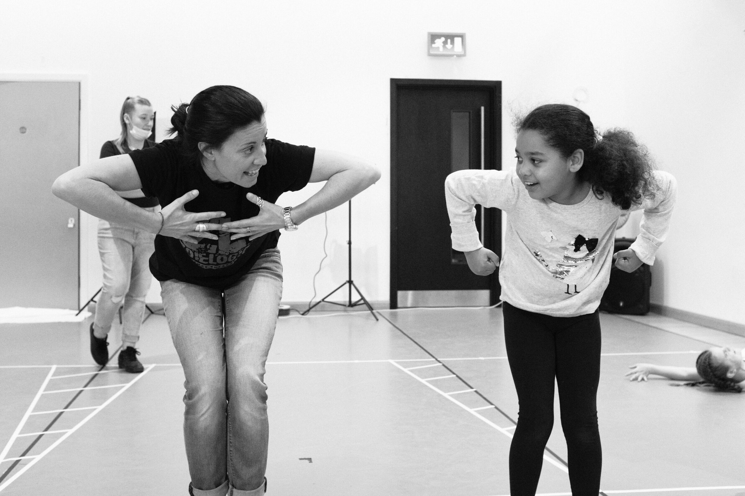 A dance facilitator works with a young girl in a dance studio