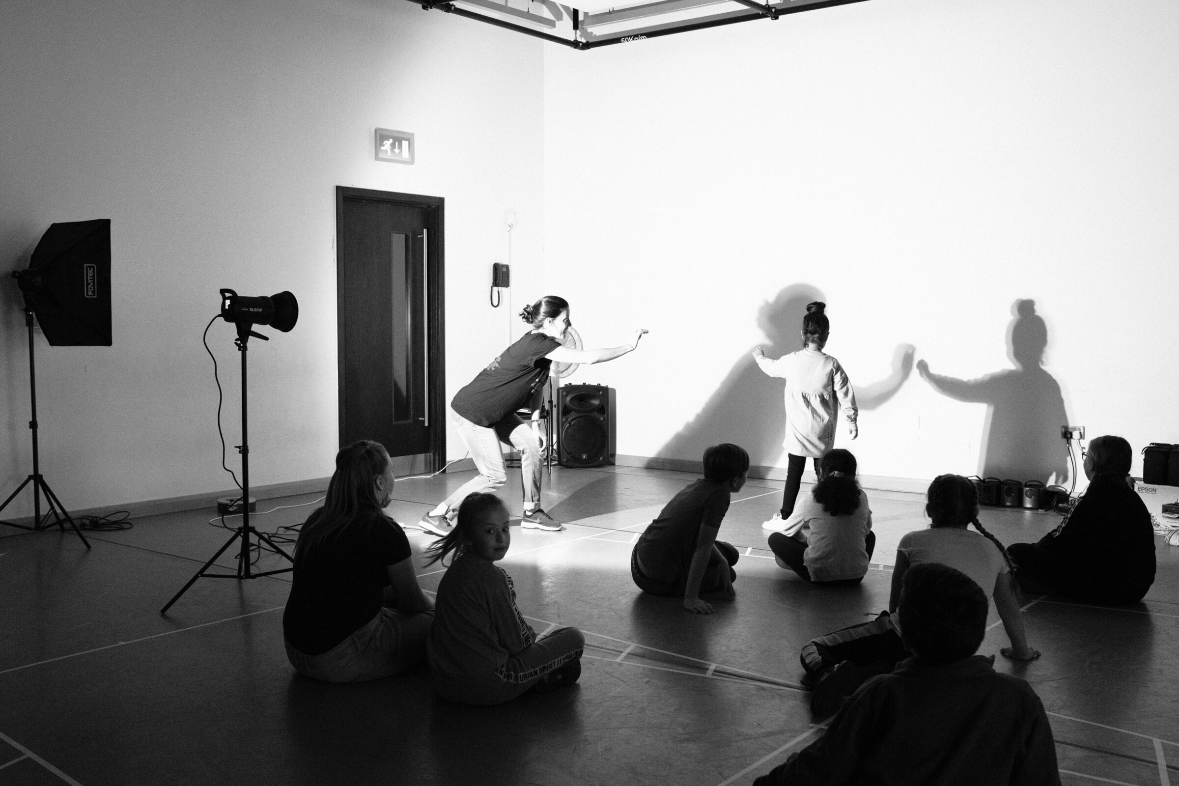 A dance facilitator and child work together with their shadows in against a wall