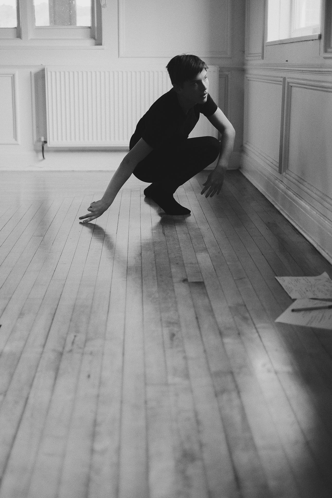 A teenage boy dances on the floor during a dance rehearsal