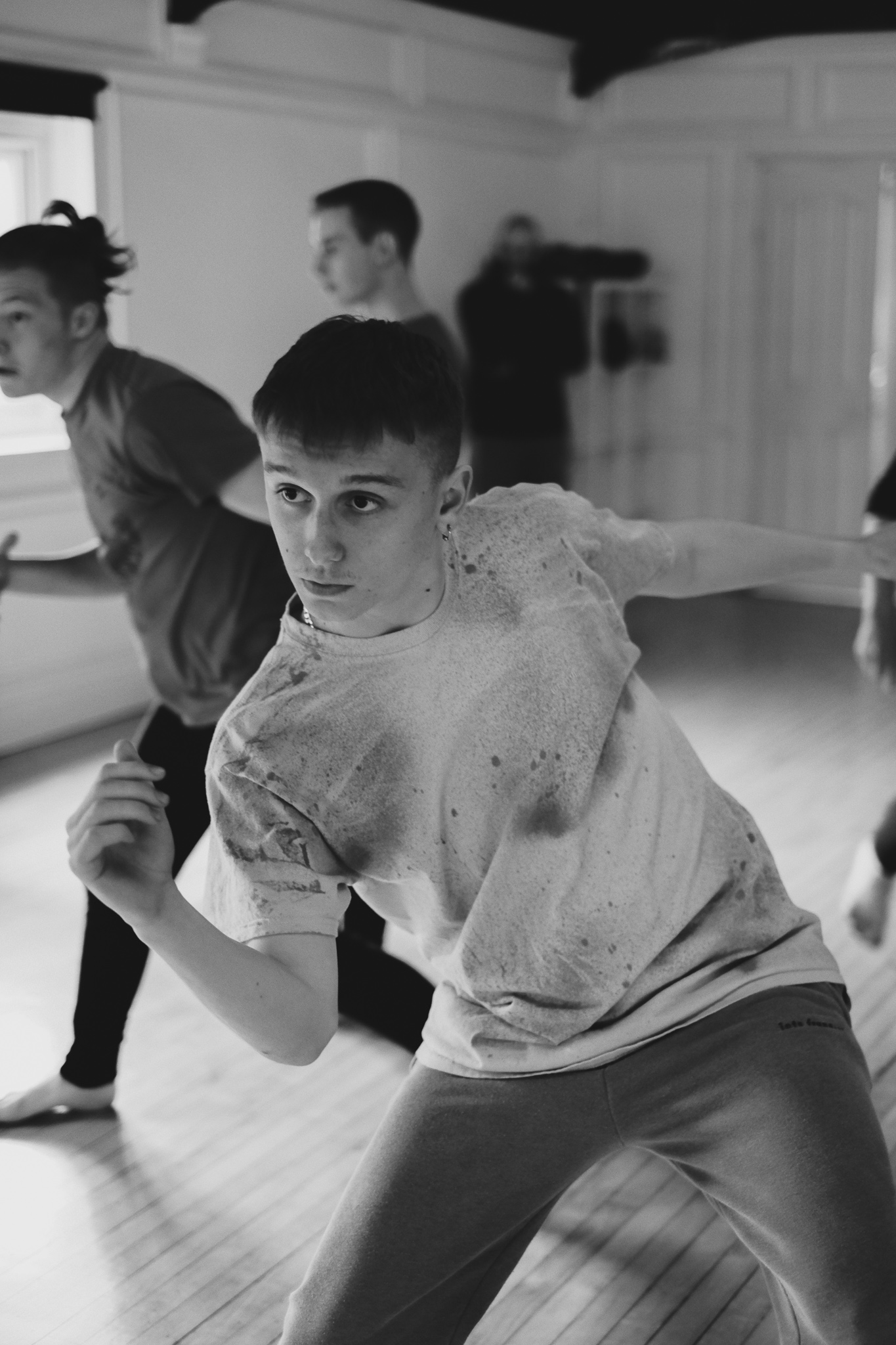 A group of teenage boys move together during a dance rehearsal