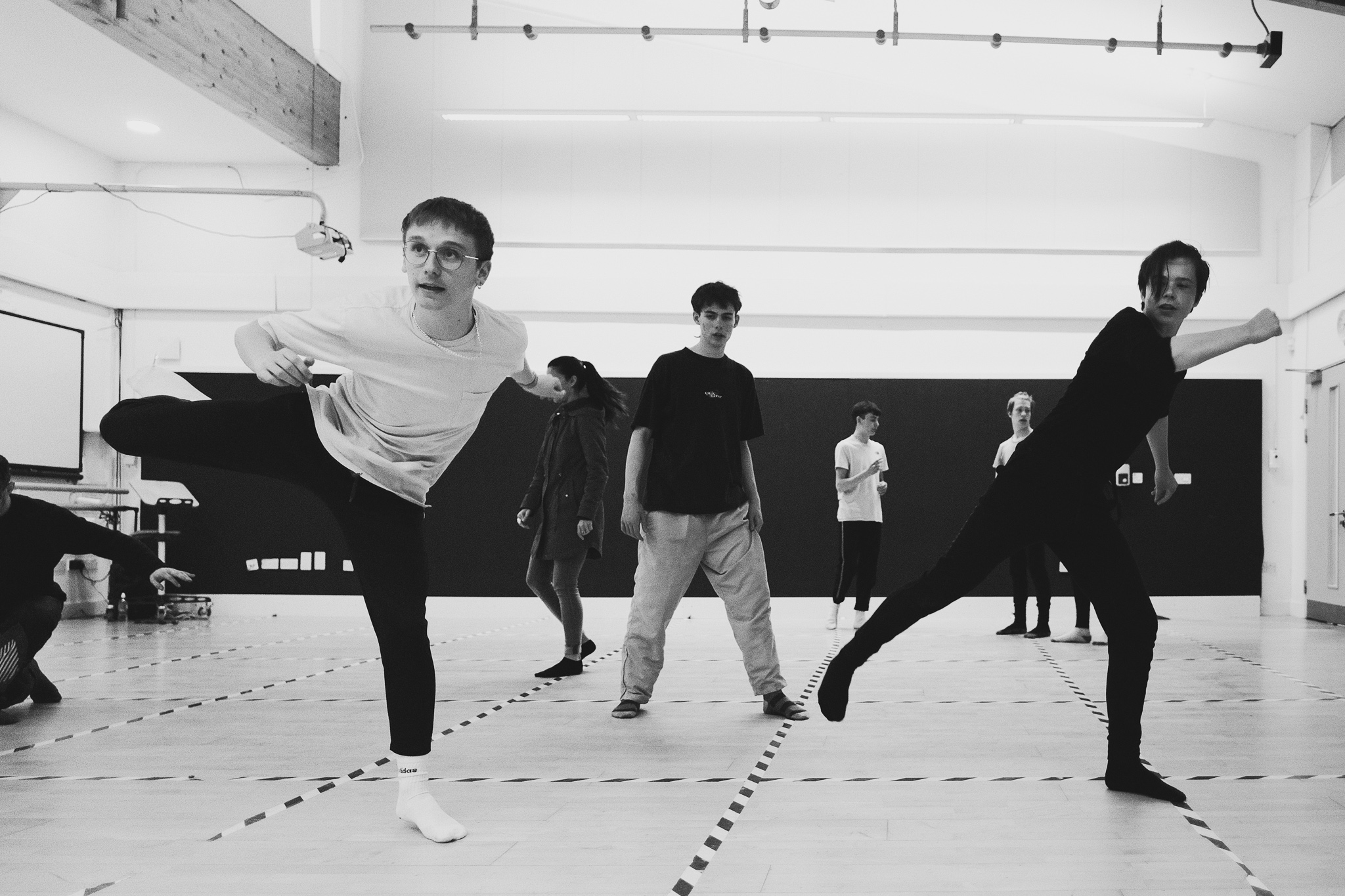 A group of teenage boys dance in a rehearsal studio. They are swinging their legs our while another looks on from behind