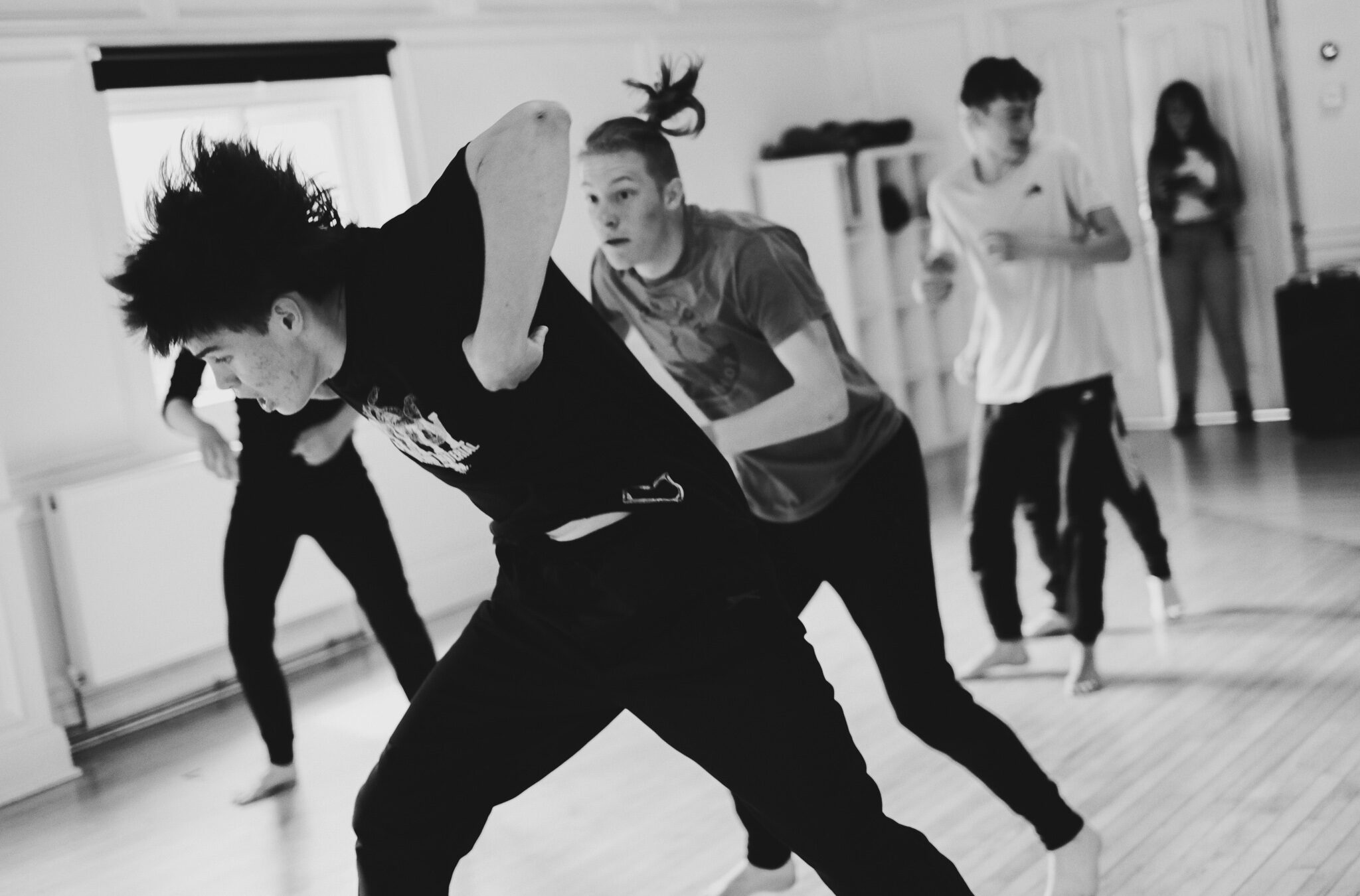 A group of young men dance in a rehearsal studio. The figure at the front throws himself forward with his arms raised