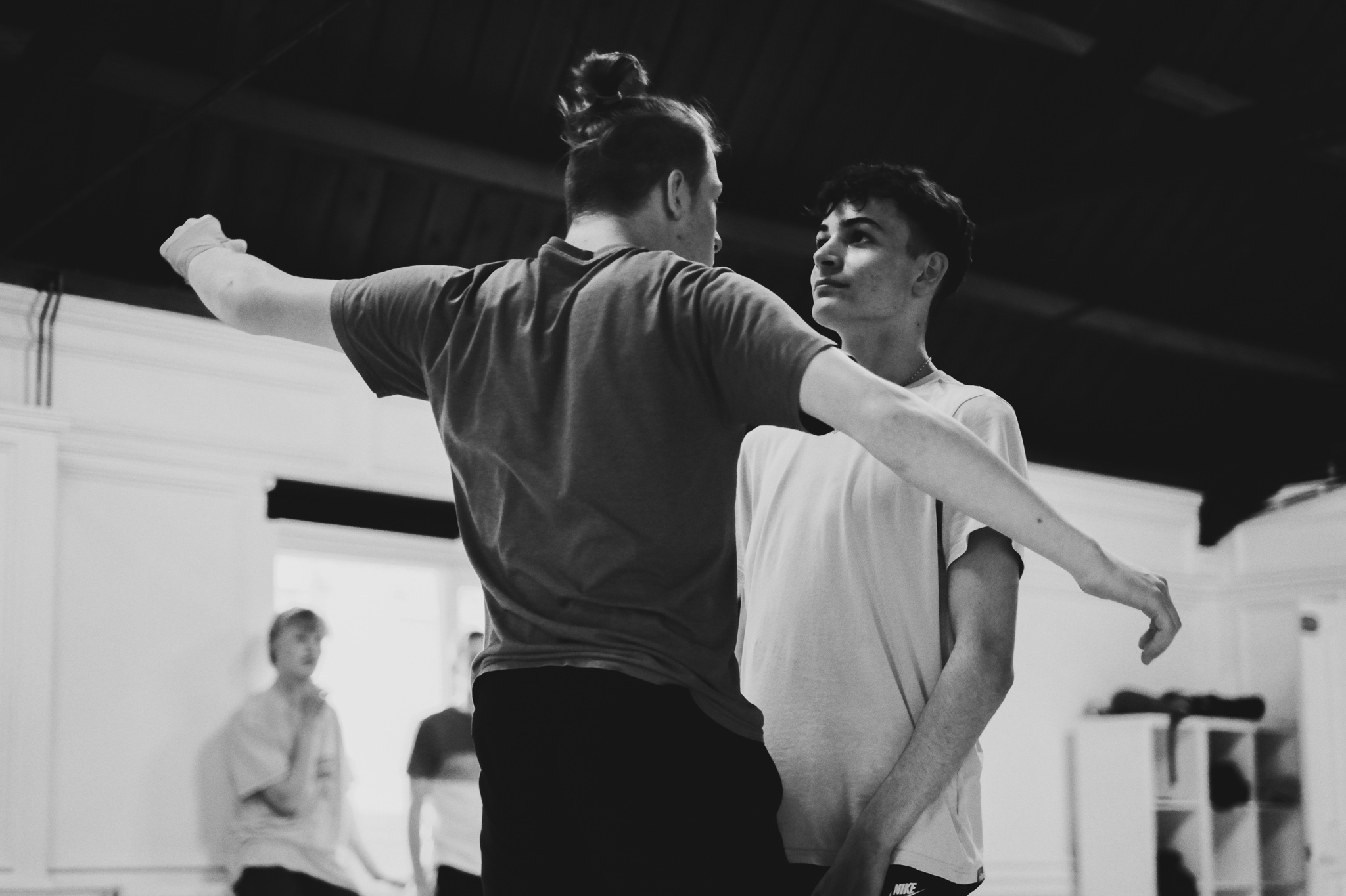 Two teenage boys face each other during a dance rehearsal, one has his arms raised, while the other stares at him directly