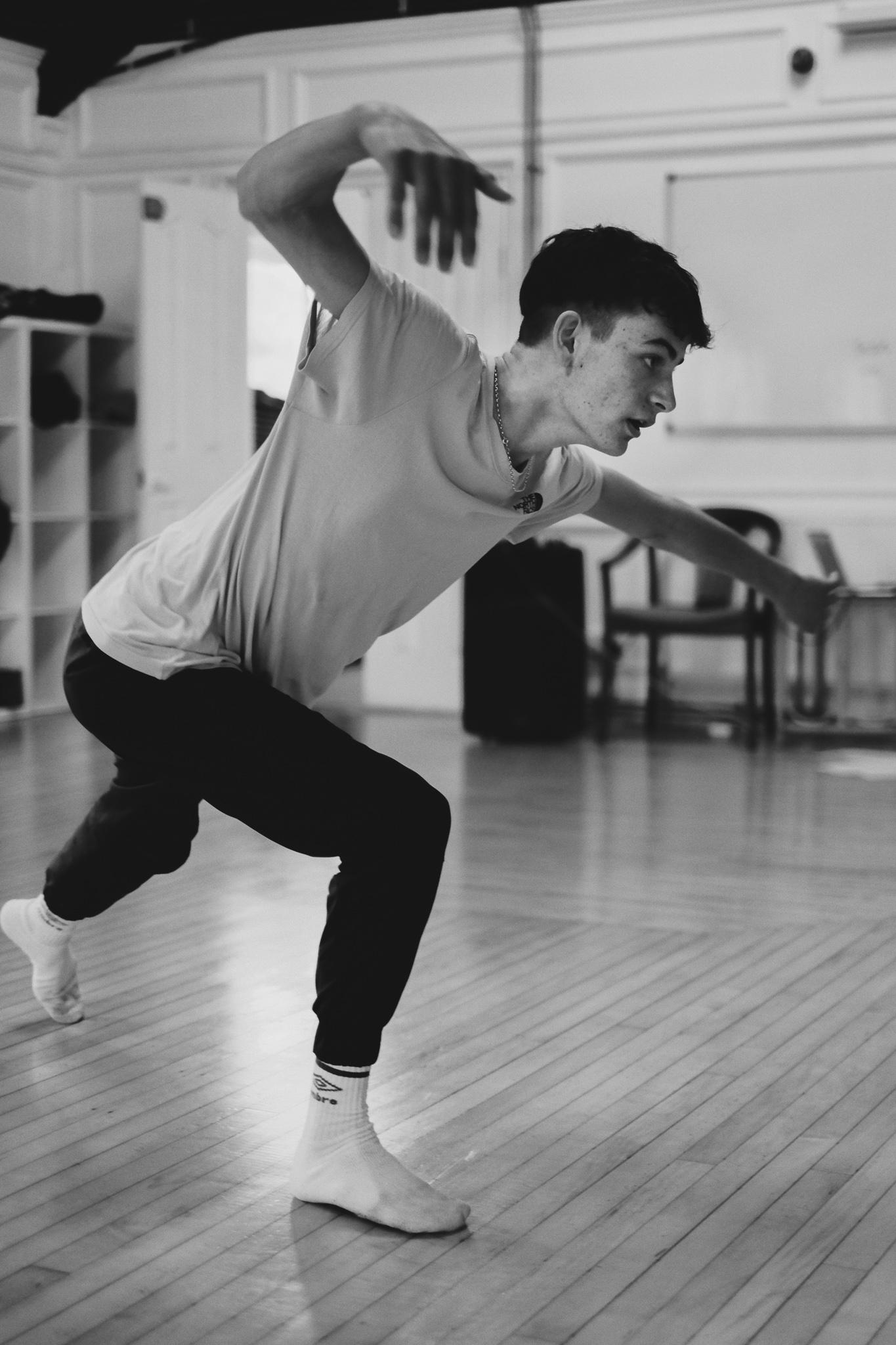 A teenage boy lunges forward during a dance rehearsal