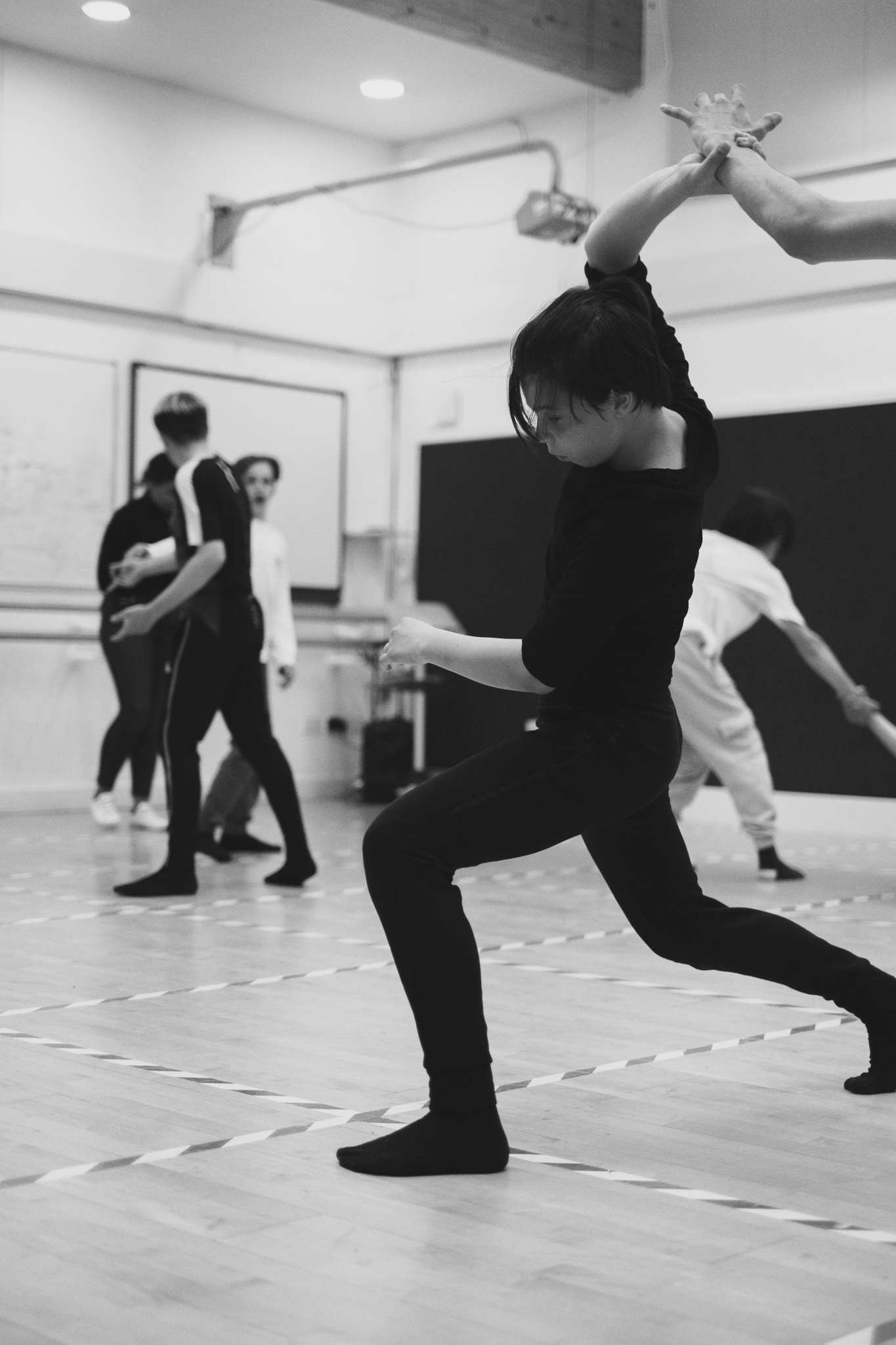 A teenage boy dances during a dance rehearsal, his hand is connected to another