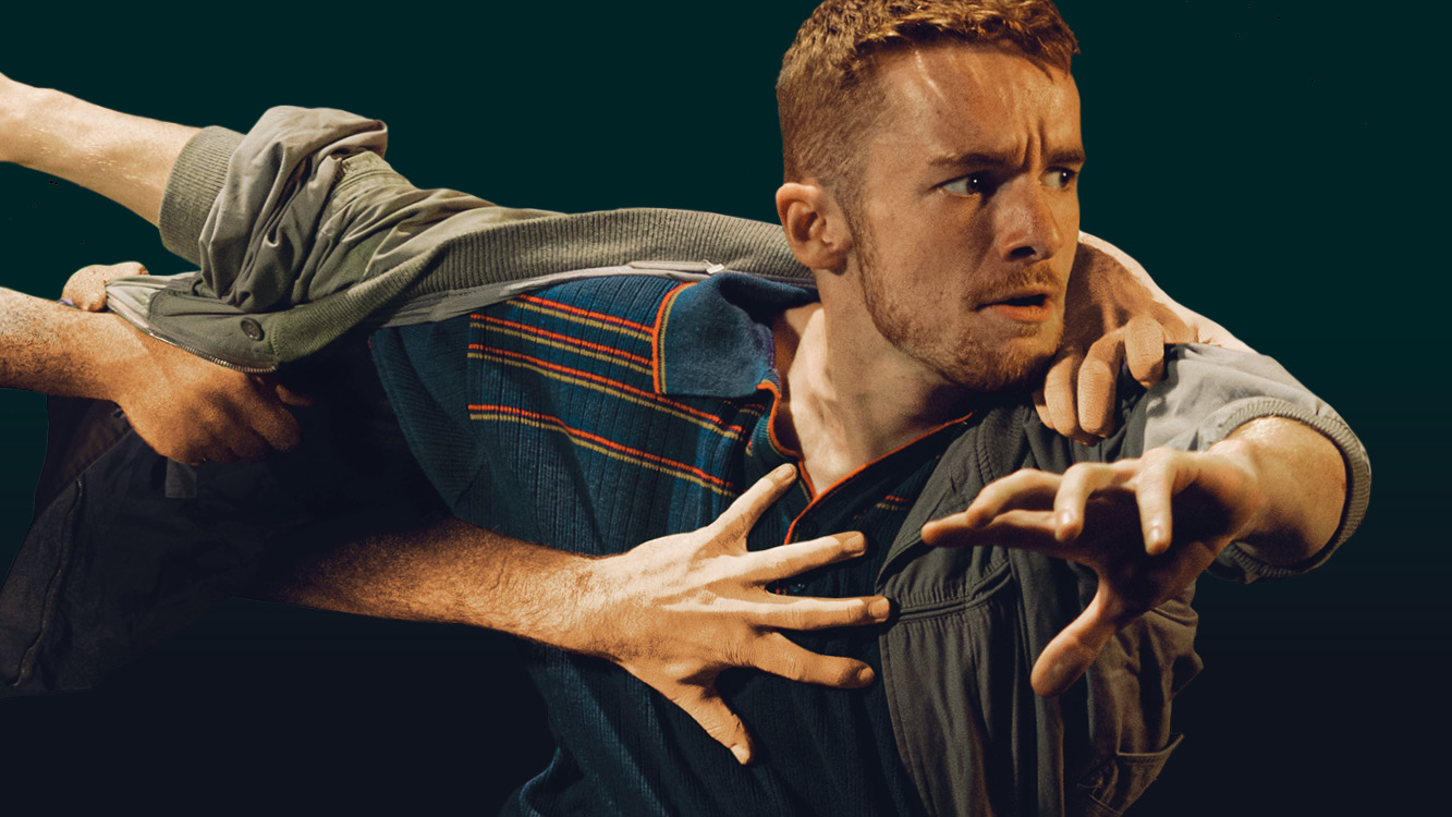 A white man with short red hair wearing a blue and orange stripe shirt with green jacket is leaning with his arms out, as if running. There are other white hands are visible grabbing his shirt. With a black background on stage.
