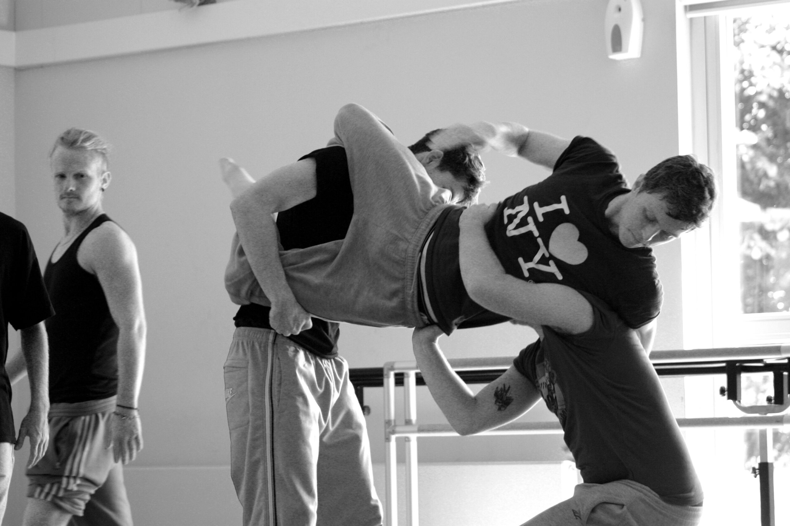 Dancers lifting each other up in rehearsal