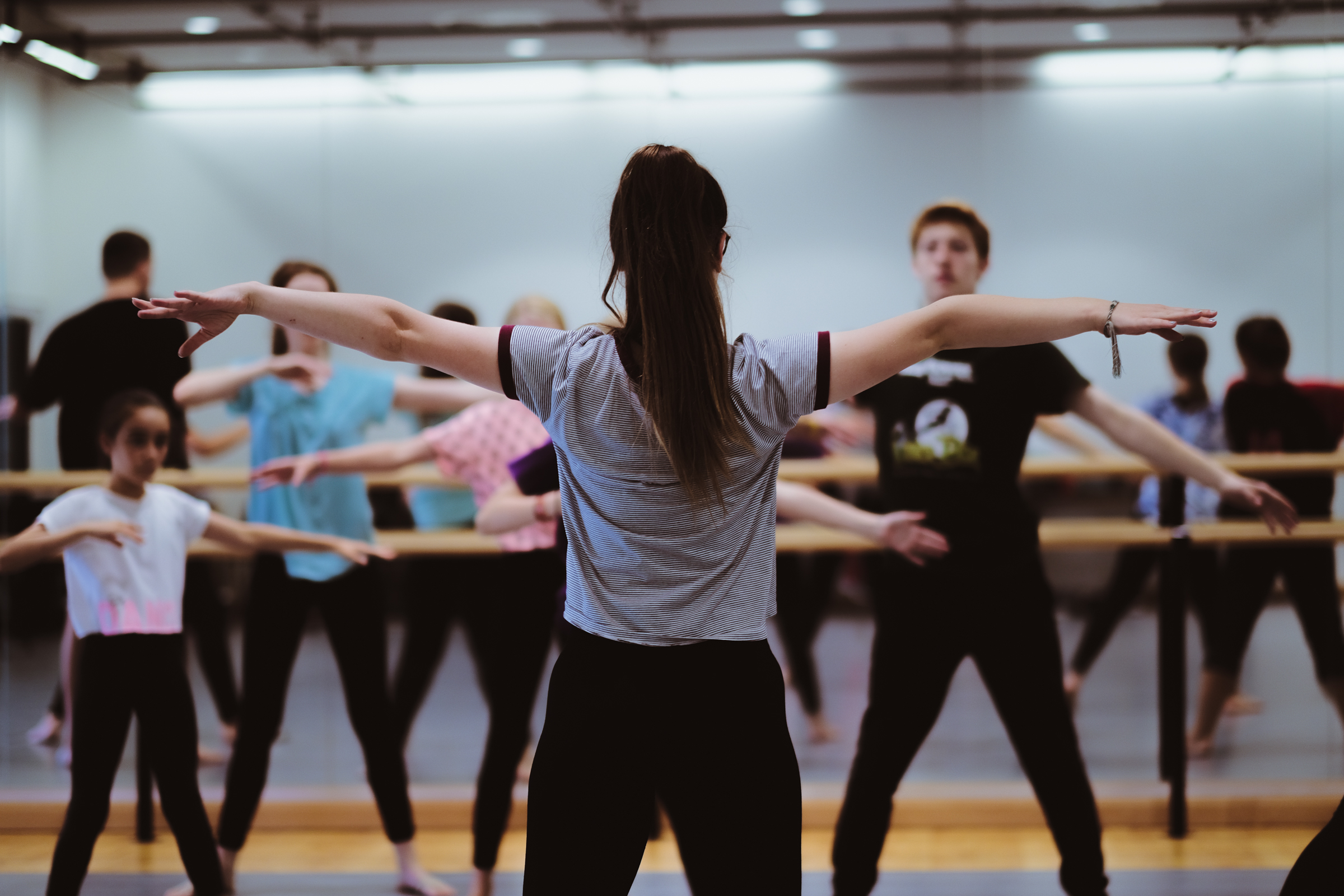 Dancers in rehearsal with arms stretched out