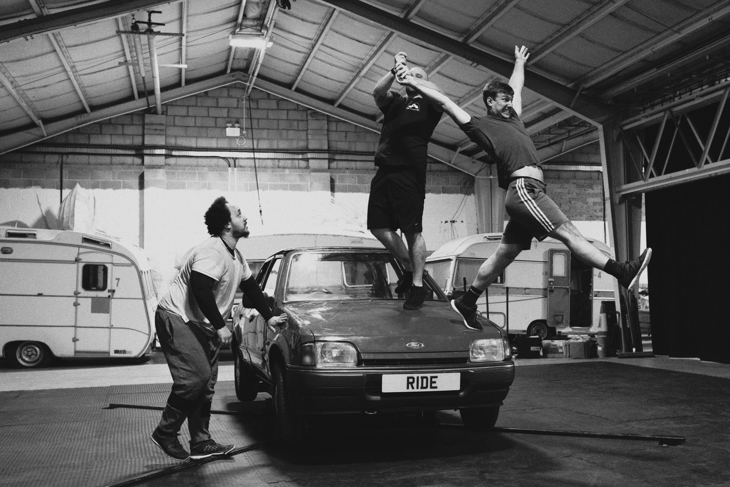 Three dancers rehearsing on top of a car