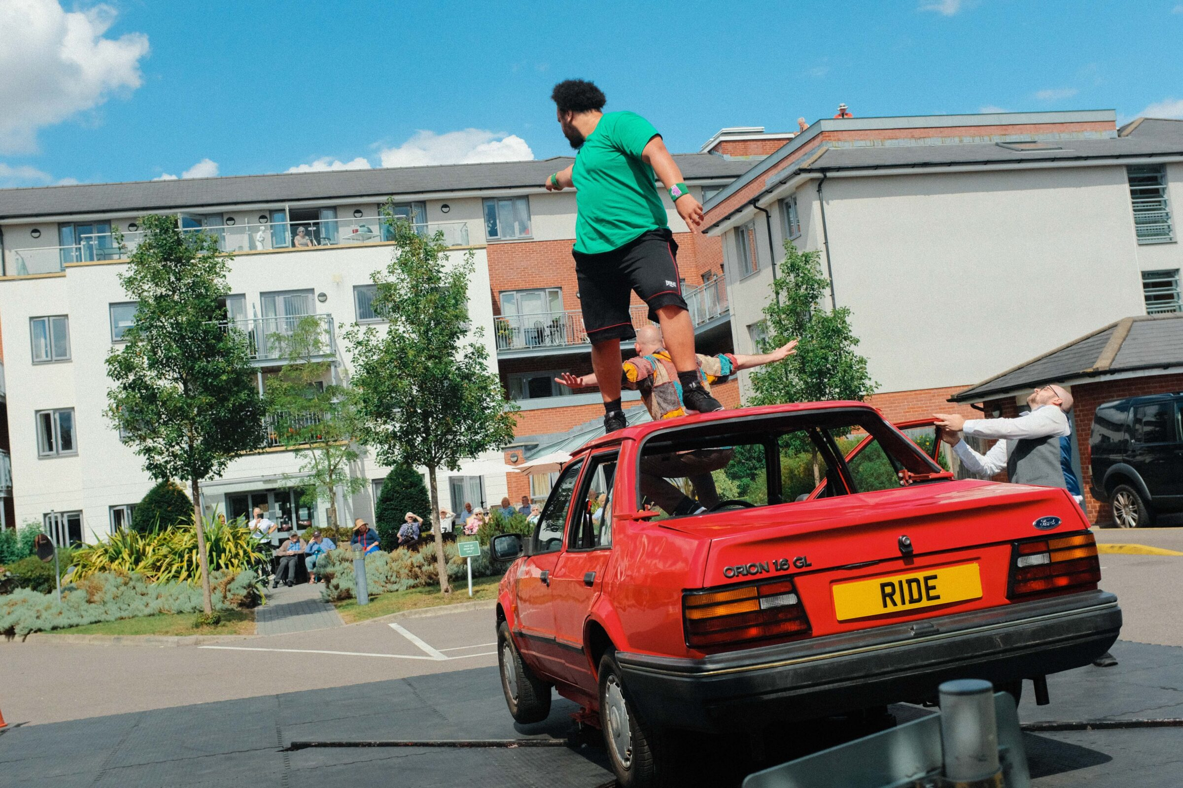 A Black Caribbean and white mixed heritage man with a black beard and short curly black hair in a green t shirt and black shorts stands on top of red Ford Orion car in a carpark, pointing towards a building with trees around it.