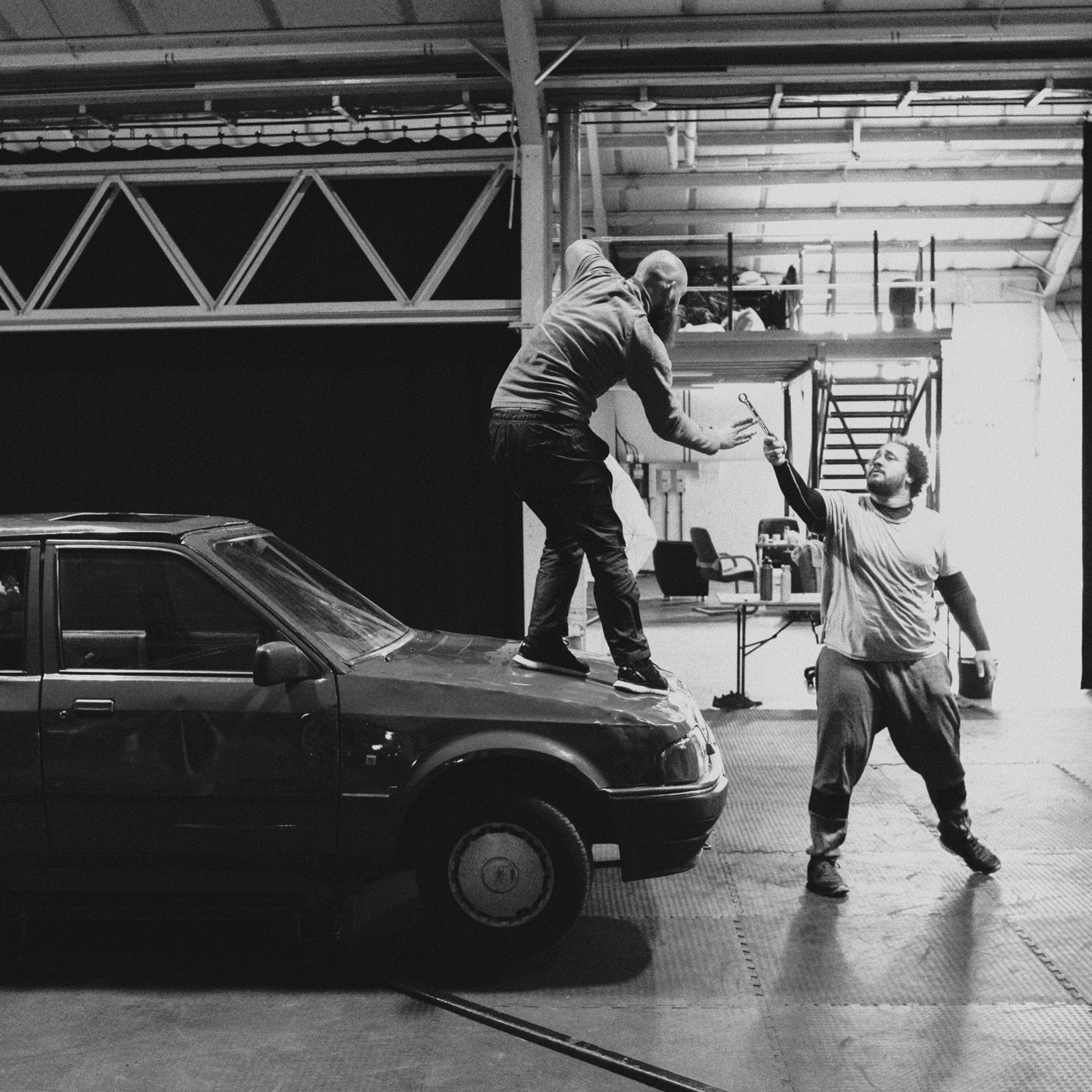 Two dancers rehearsing on a car
