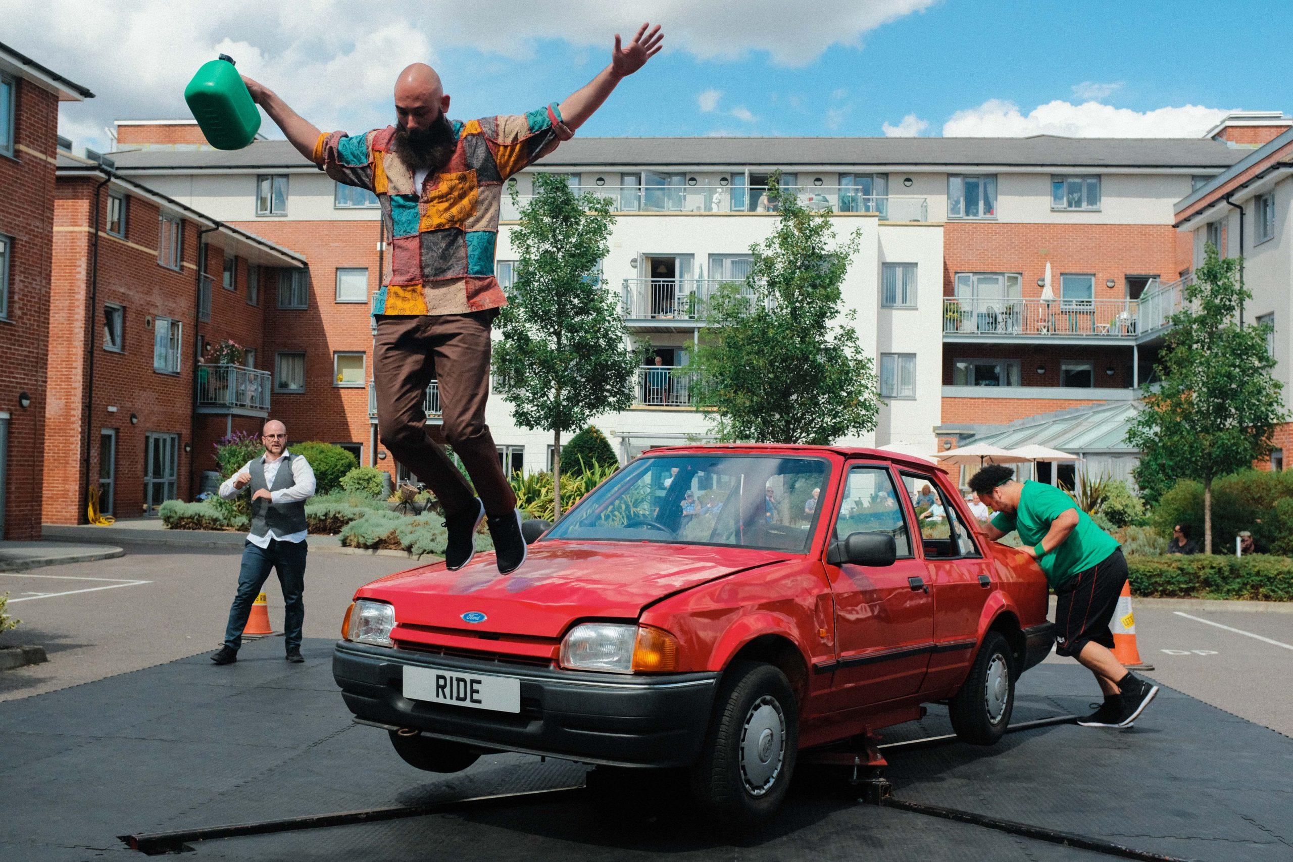 Dancer jumps off the front of a car