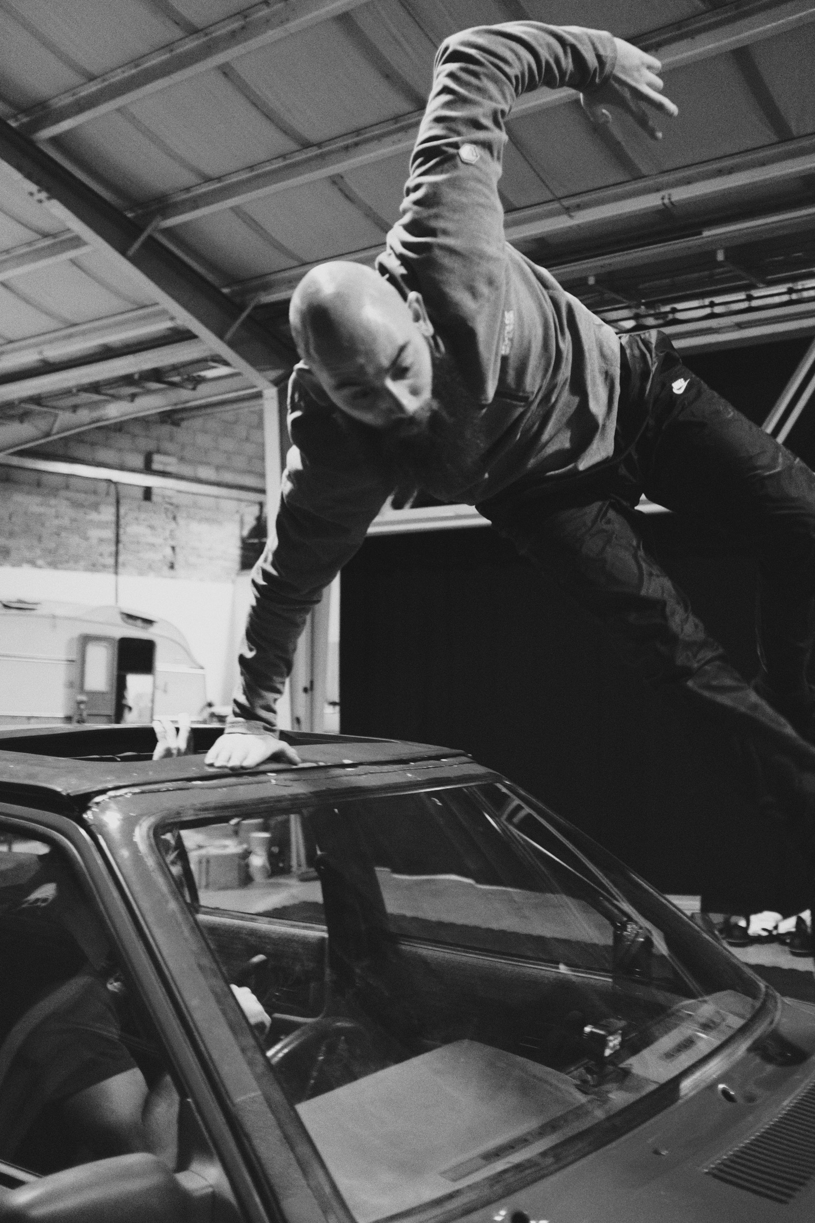 A dancer jumping off the top of a car