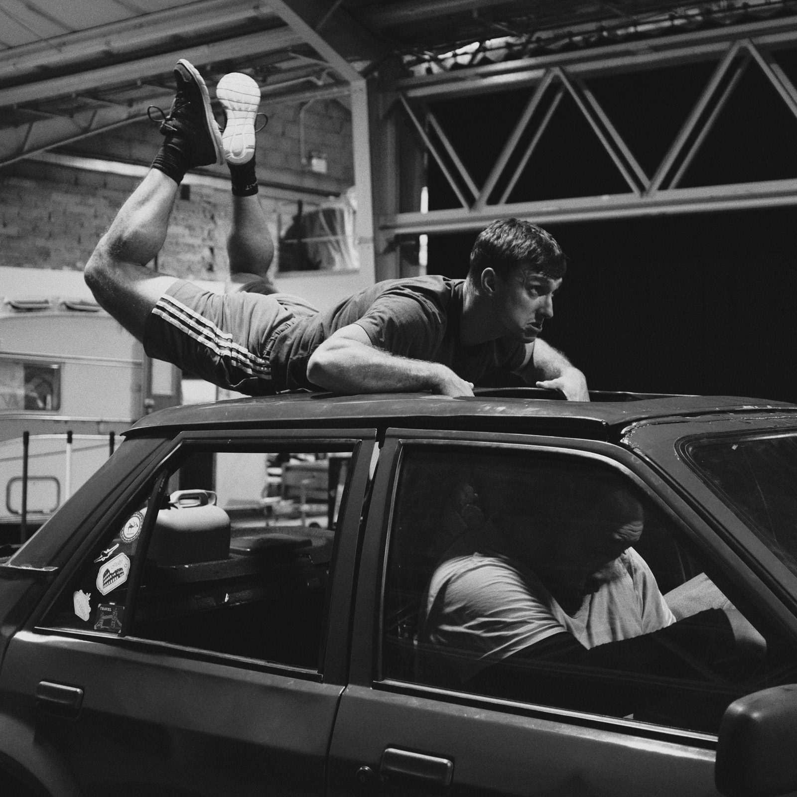 A dancer rehearsing on top of a car