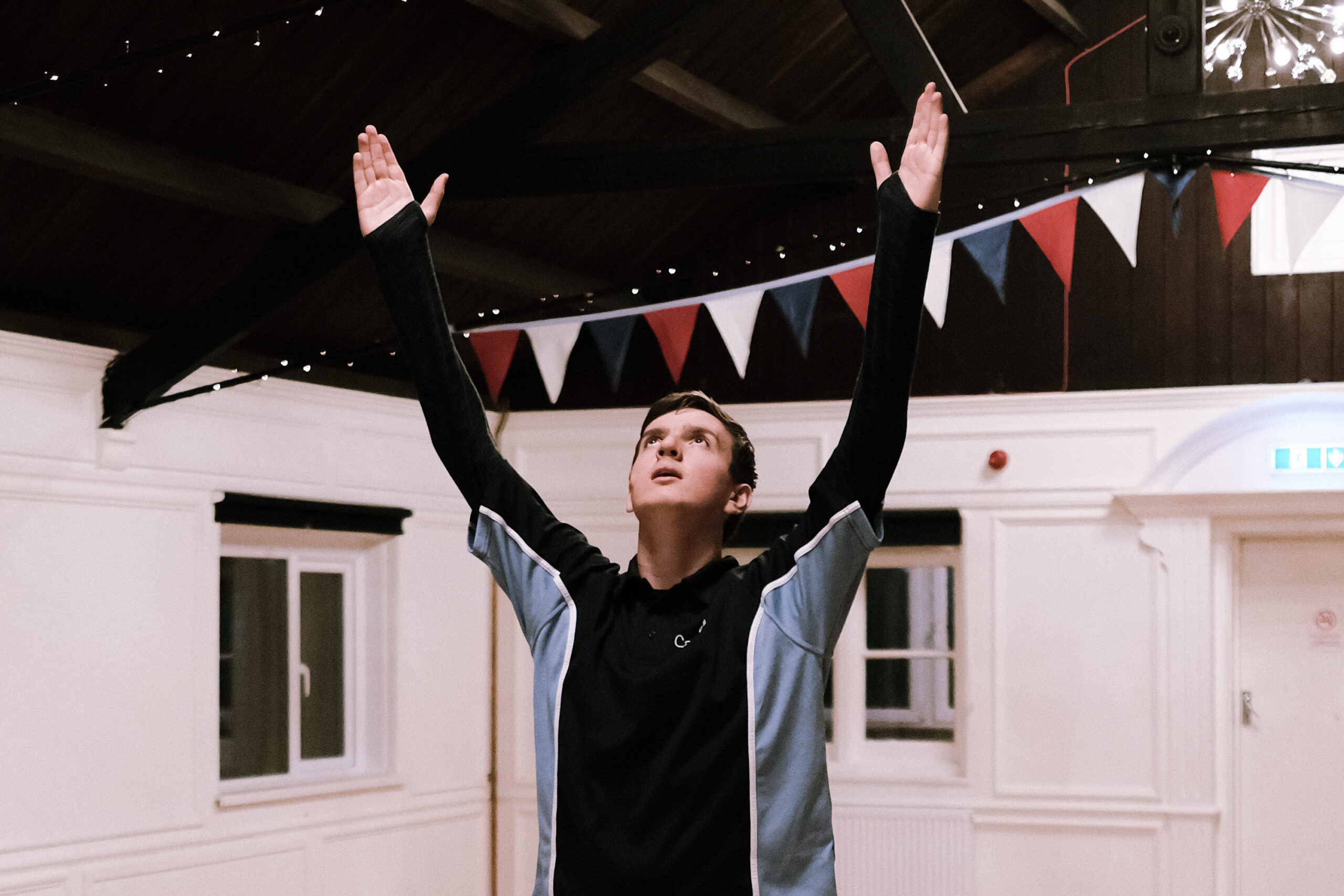 A young dancer rehearsing with arms reaching up into the air
