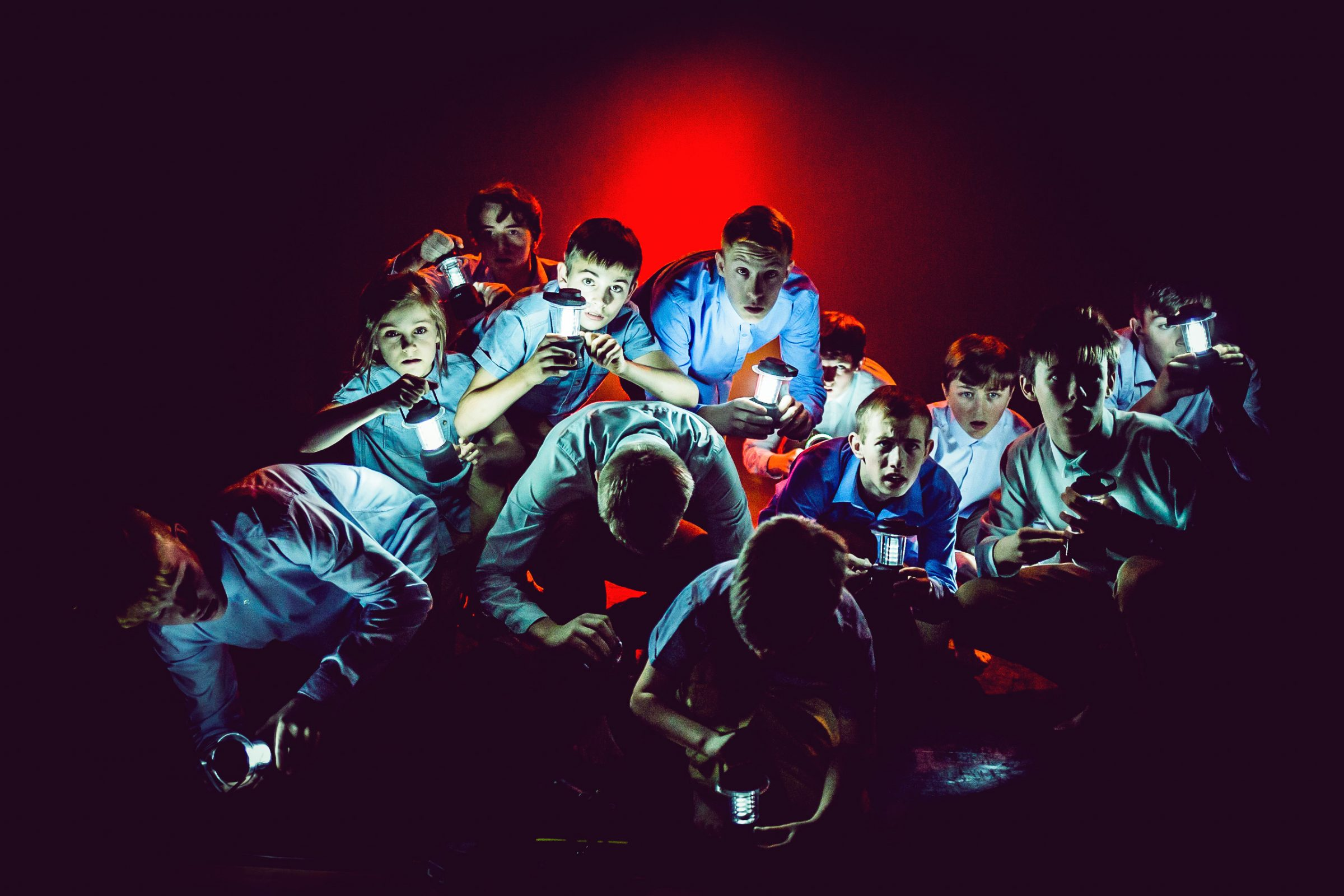 group of boys on a dark stage, shining torch lights in front of red back lighting. The boys are wearing blue tops and trousers and looking curious as they crouch in a huddle.