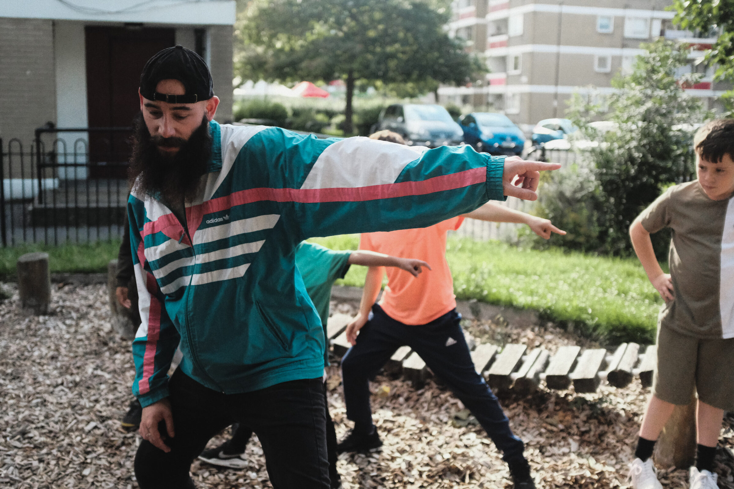 A dance artist works with the young people of Holyrood estate in Southampton. They are working in the park with arms outstretched