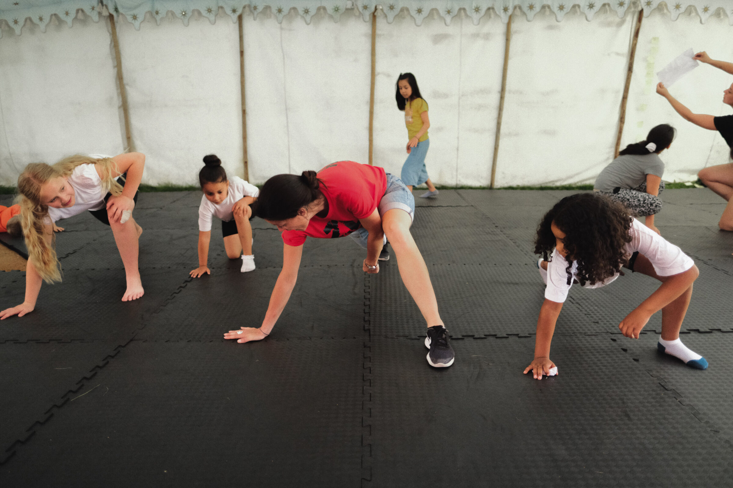 A dance facilitator works with the young people of the Holyrood estate. They are learning a new dance technique using the floor