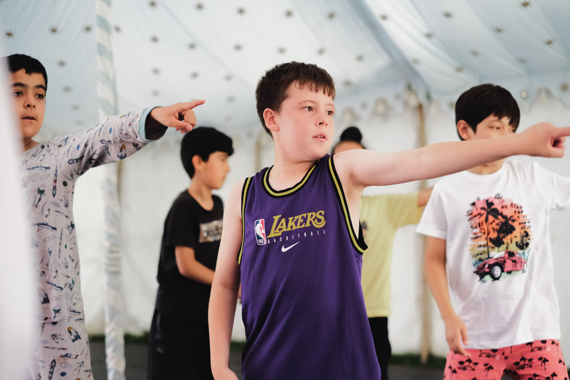 A group of young people perform inside a tent. They have their left arm outstretched and pointing into the distance