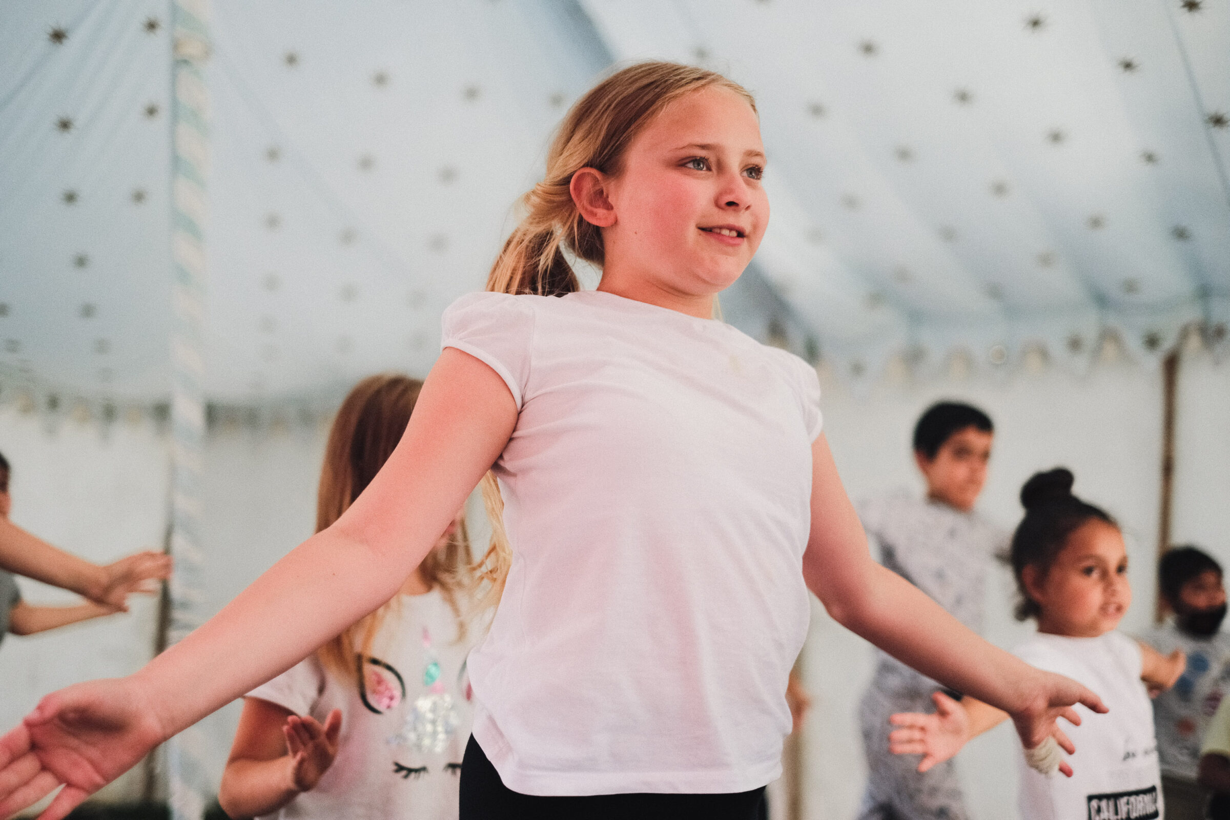 A young person performs a dance move as other young people dance in the background