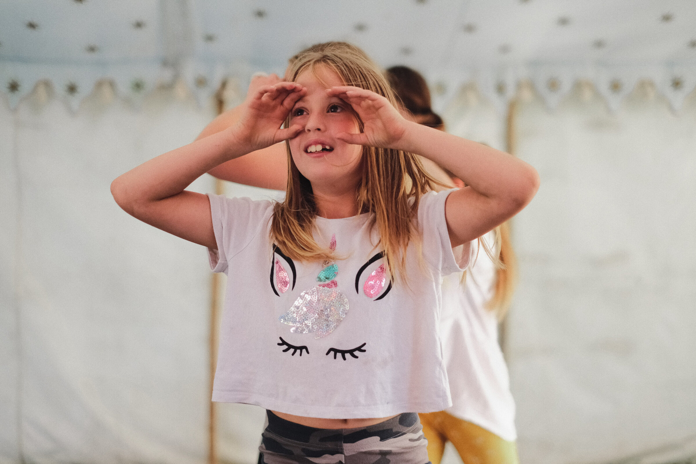A young person is dancing with her hands held up to her face to create an imaginary pair of binoculars