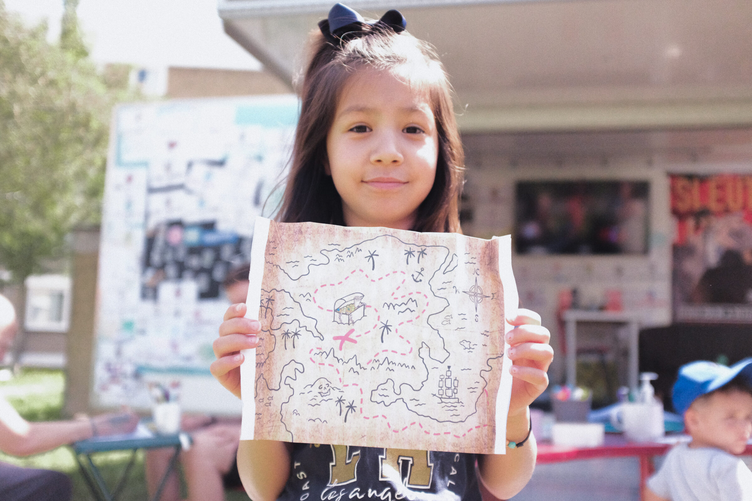 A young person poses for a portrait while holding up a treasure map