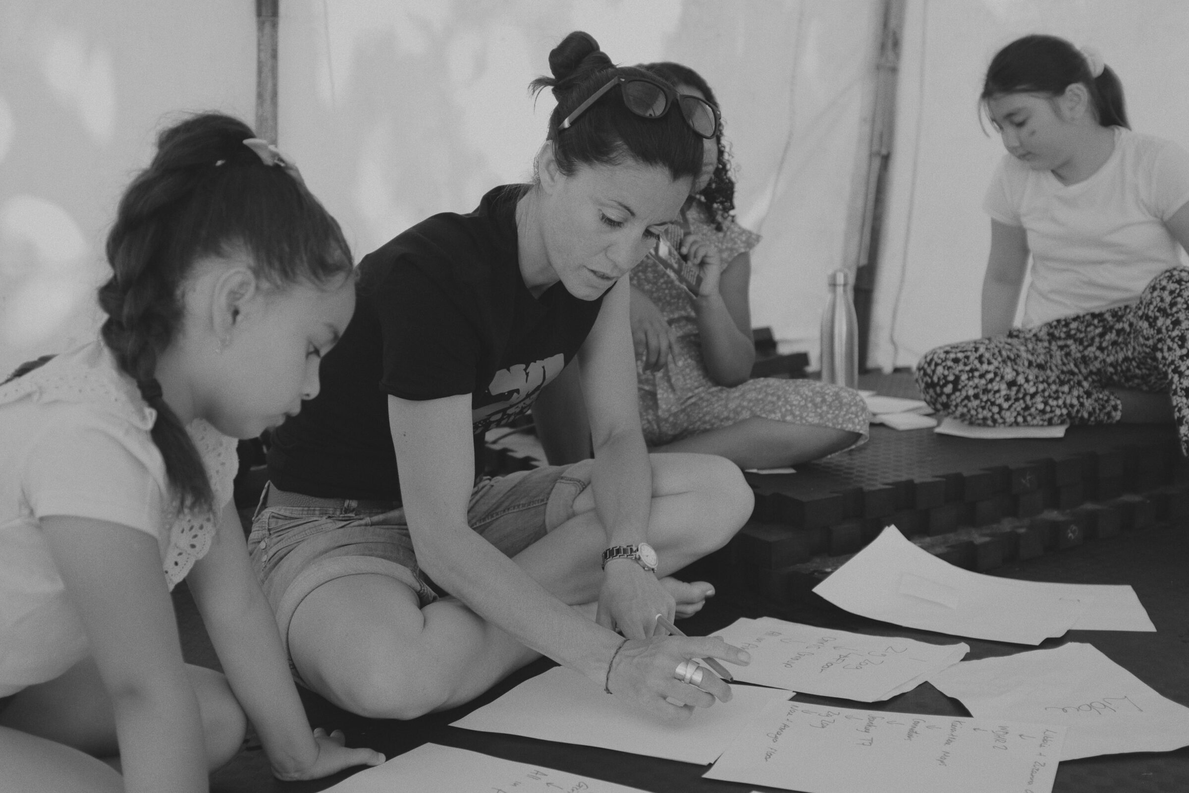 A dance facilitator sits and plans on pieces of paper and is surrounded by the young people of the Holyrood estate