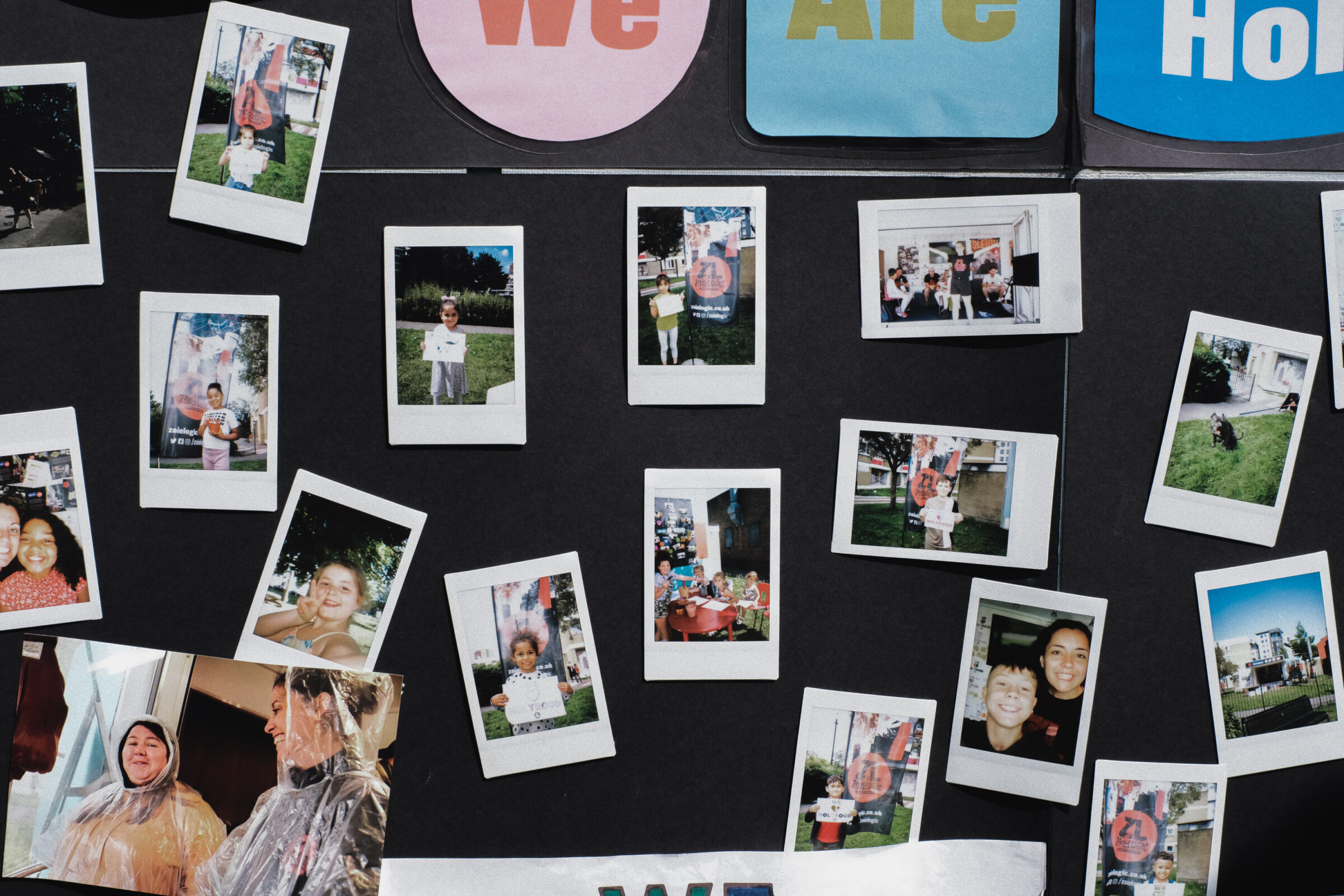 A selection of instant camera prints on a display. The pictures feature selfies and portraits of the young people of Holyrood estate