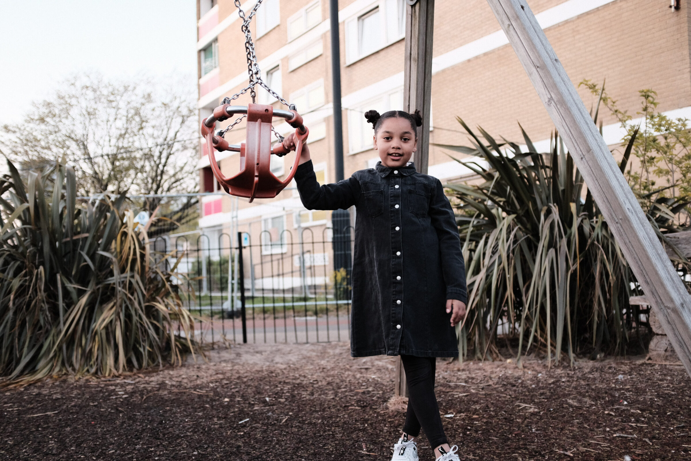 A girl poses next to a set of swings with buildings in the background